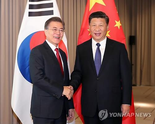 资料图片:当地时间7月6日上午,在德国柏林,韩国总统文在寅(左)和中国国家主席习近平会晤,双方亲切握手。(韩联社)