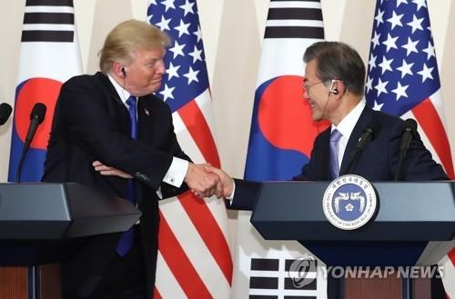 11月7日,在青瓦台,韩美两国总统在首脑会谈后举行的记者会上握手。(韩联社)