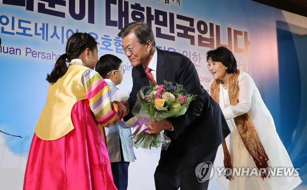 当地时间11月8日下午,在雅加达一家酒店,韩国总统文在寅和夫人金正淑女士接过小朋友送上的花束。(韩联社)
