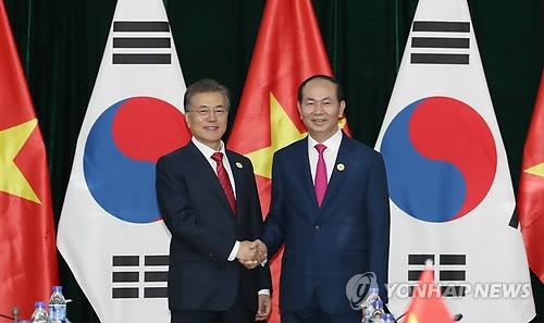 当地时间11月11日,在越南岘港,韩国总统文在寅(左)与越南国家主席陈大光合影。(韩联社)
