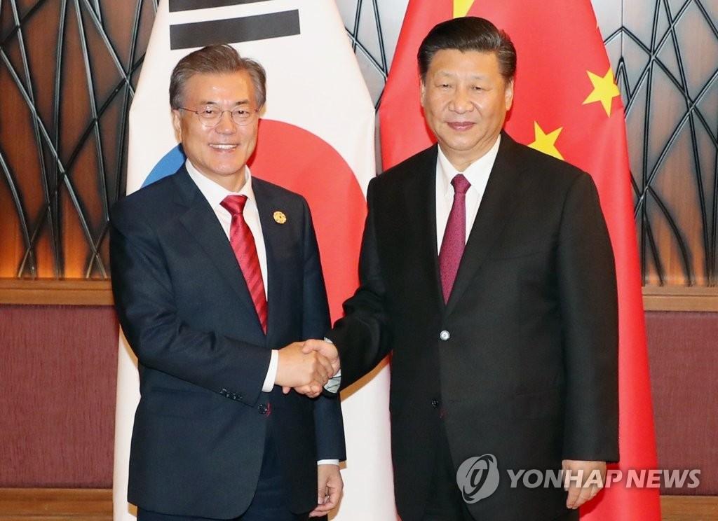 当地时间11月11日,在越南岘港,韩国总统文在寅(左)与中国国家主席习近平在会谈前握手合影。(韩联社)