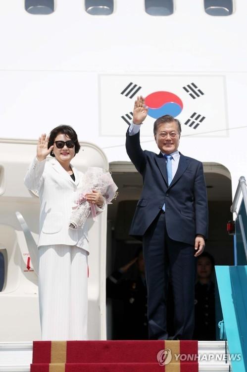 当地时间11月12日,在越南岘港国际机场,韩国总统文在寅(右)与夫人金正淑女士向送行人群挥手道别。当天,文在寅结束亚太经合组织(APEC)峰会日程,转赴菲律宾出席东盟系列会议。(韩联社)
