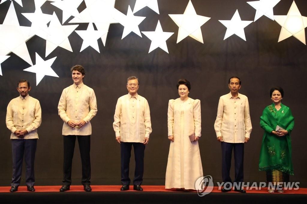 当地时间11月12日下午,在马尼拉SMX会展中心,韩国总统文在寅(左三)和第一夫人金正淑女士(右三)与各国领导人在东盟50周年晚宴合影。(韩联社)