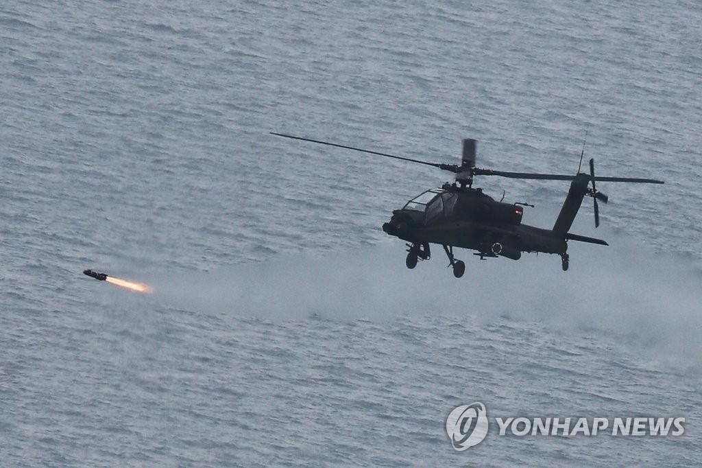 """11月13日,在全罗北道群山前海射击场,韩国陆军航空作战司令部麾下8架阿帕奇卫士(AH-64E)攻击型直升飞机实弹发射""""地狱火""""空地导弹。(韩联社/韩陆军提供)"""