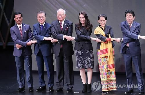 当地时间11月13日上午,在菲律宾马尼拉,韩国总统文在寅(左二)出席在菲律宾文化中心举行的第31届东盟首脑会议开幕式并与各国领导人拉手合影。(韩联社)
