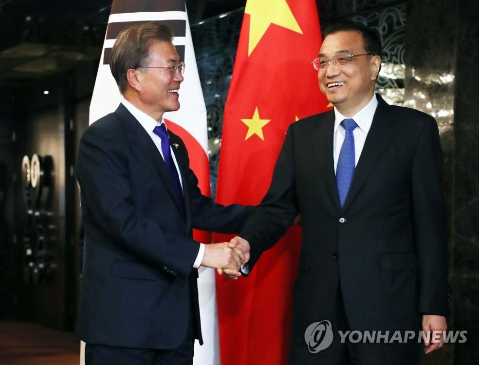 11月13日下午,在菲律宾马尼拉,韩国总统文在寅(左)和中国国务院总理李克强在举行会谈前握手合影。(韩联社)