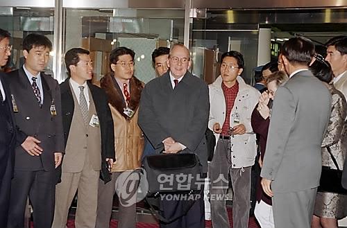 资料图片:1997年12月3日,在首尔金浦机场,时任IMF总裁米歇尔·康德苏(中)抵韩后回答记者提问。(韩联社)