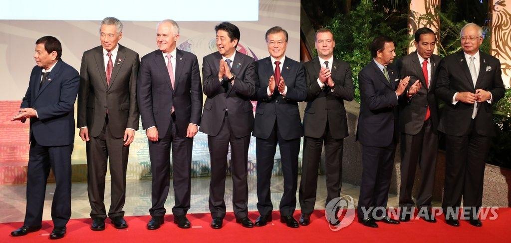 11月14日下午,在马尼拉国际会议中心,第12届东亚峰会前,韩国总统文在寅(中)同各国首脑合影。左起为菲律宾总统罗德里戈·杜特尔特、新加坡总理李显龙、澳大利亚马尔科姆·特恩布尔、日本首相安倍晋三、文在寅、俄罗斯总理梅德韦杰夫、文莱国王哈吉·哈桑纳尔·博尔基亚、印尼总统佐科维、马来西亚总理纳吉布。(韩联社)