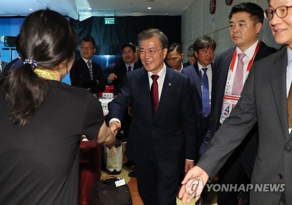 11月14日下午,在菲律宾马尼拉今旅酒店的中央记者室,文在寅在亚太经合组织、东盟首脑会议等首次东南亚访问成果发布会结束后与记者亲切握手。(韩联社)