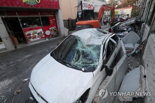 11月15日,在浦项北区兴海邑,地震导致一超市外墙倒塌砸坏汽车。(韩联社)