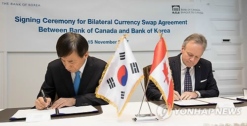 当地时间11月15日下午,在渥太华的加拿大中央银行,李柱烈(左)与波洛兹签署韩加货币互换协议。(韩联社)