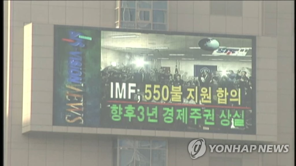 资料图片:1997年亚洲金融危机时,电视台在播出国际币基金组织决定向韩国提供援助贷款的消息。(韩联社)