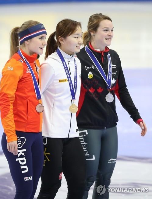 11月19日,在首尔木洞滑冰场,崔珉祯(中)站在领奖台上与银、铜牌得主合影留念。(韩联社)