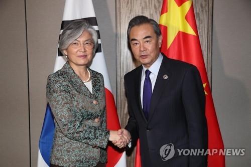 资料图片:8月6日,在马尼拉,韩国外长康京和(左)与中国外长王毅握手合影。(韩联社)