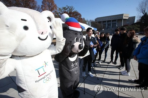 """资料图片:平昌冬奥会吉祥物白老虎""""Soohorang""""和亚洲黑熊""""Bandabi""""现身大学校园。(韩联社)"""