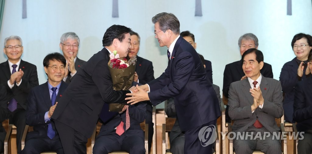 11月21日上午,文在寅总统(右)向中小风险企业部长官洪钟学颁发任命书。(韩联社)