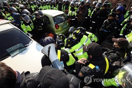 """11月21日上午,在庆尚北道星州""""萨德""""基地附近,警察强制解散阻止施工车辆驶入的当地居民。(韩联社)"""
