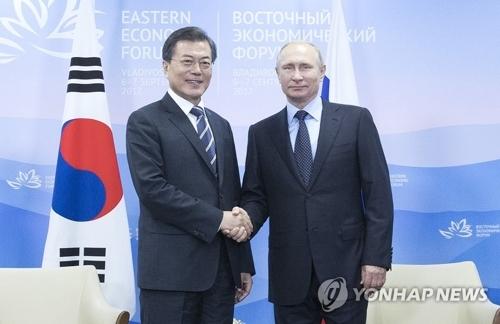 资料图片:当地时间9月6日下午,在俄罗斯符拉迪沃斯托克远东联邦大学,韩国总统文在寅(左)与俄罗斯总统普京举行会谈前握手。(韩联社)