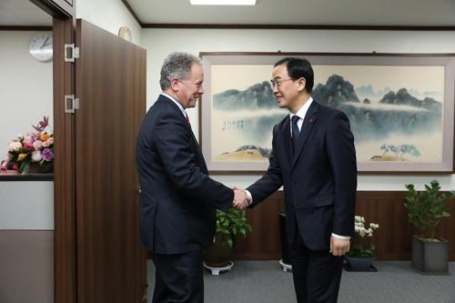 11月22日,韩国统一部长官赵明均(右)同到访的联合国世界粮食计划署执行主任戴维·比斯利举行会晤,图为双方握手合影。(韩联社/统一部提供)