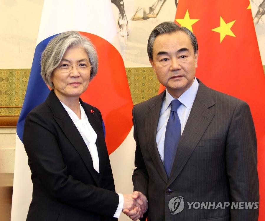 资料图片:11月22日下午,在北京钓鱼台国宾馆,韩国外交部长官康京和(左)同中国外交部长王毅举行会谈前亲切握手。(韩联社)