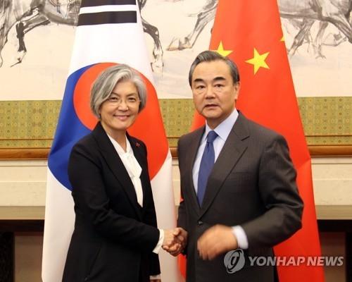 资料图片:11月22日下午,在北京钓鱼台国宾馆,韩国外交部长官康京和(左)同中国外交部长王毅举行韩中外长会谈前亲切握手。(韩联社)