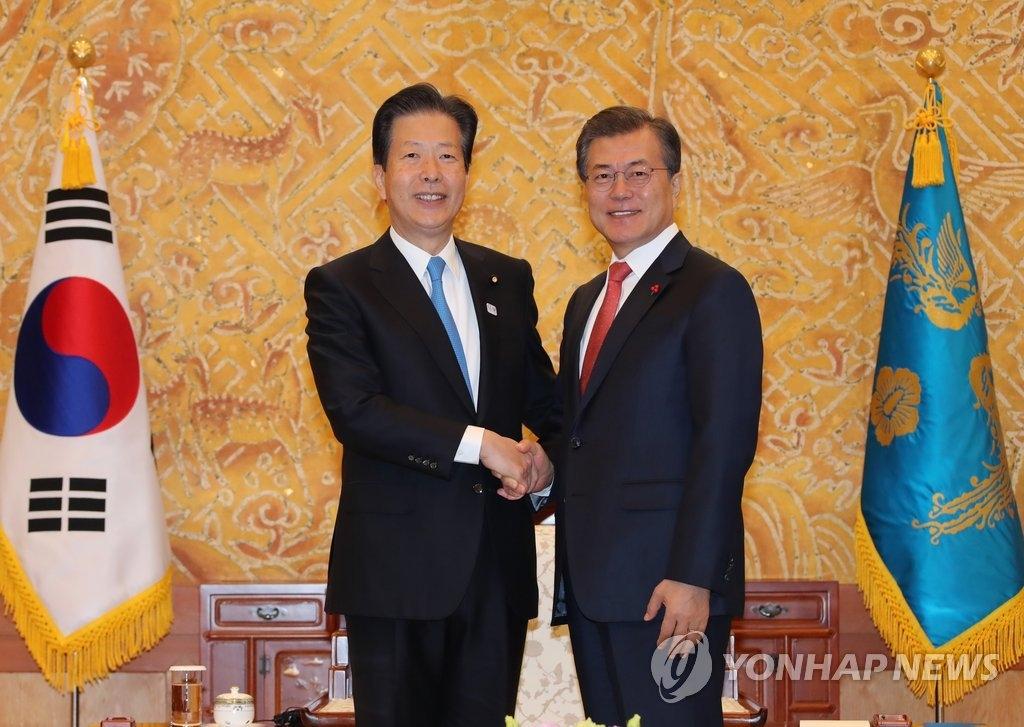 11月23日,在韩国总统府青瓦台,韩国总统文在寅(右)同日本公明党党首山口那津男握手合影。(韩联社)