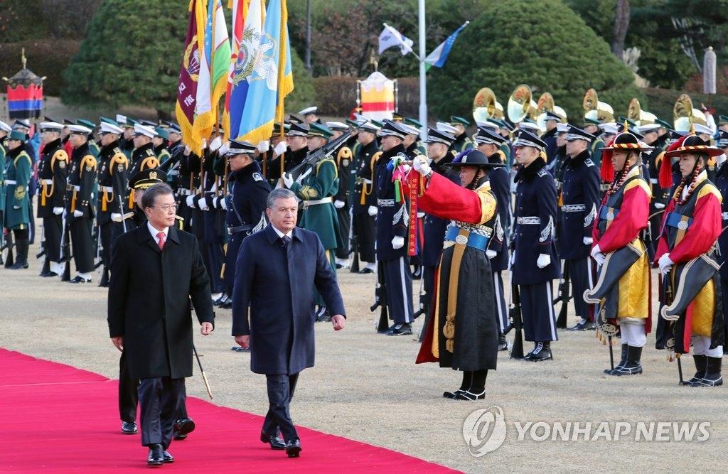 11月23日,在青瓦台,韩国总统文在寅(左)同到访的乌兹别克斯坦总统沙夫卡特·米尔济约耶夫检阅仪仗队。(韩联社)