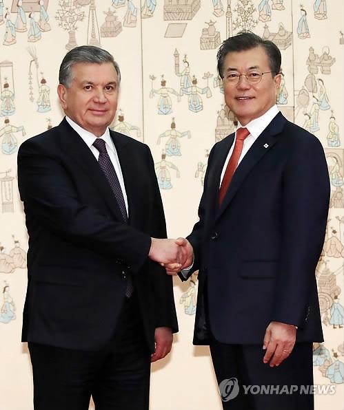 11月23日,在韩国总统府青瓦台,总统文在寅和到访的乌兹别克斯坦总统沙夫卡特·米尔济约耶夫举行会谈前握手合影。(韩联社)