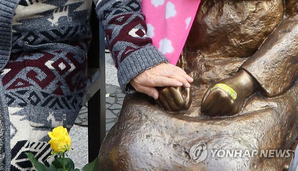 """11月22日下午,在首尔钟路区驻韩日本大使馆前,一位参与""""促进日本军慰安妇问题解决周三定期集会""""的市民与慰安妇少女铜像拉手合影。(韩联社)"""