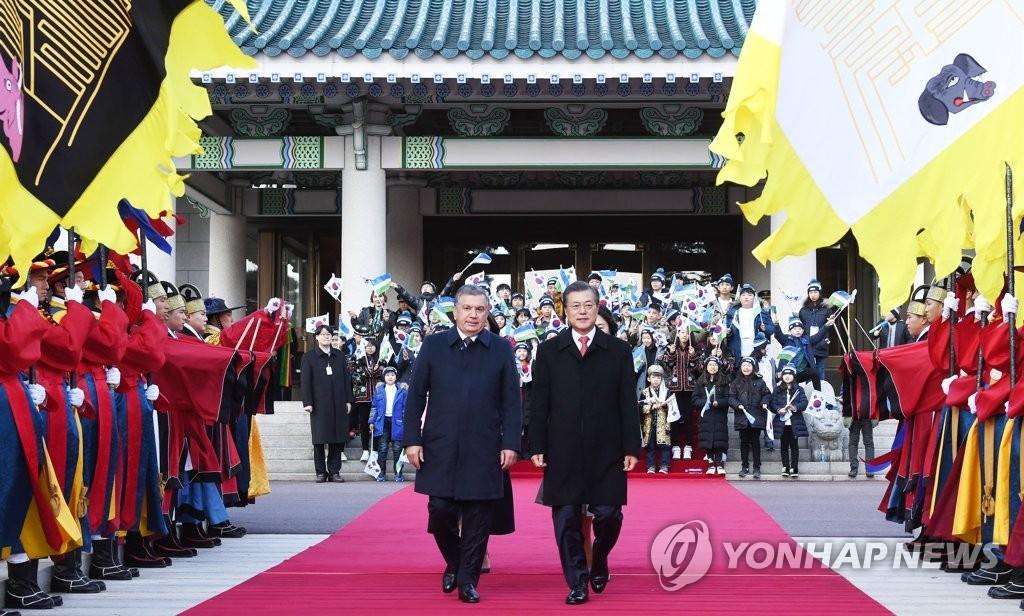 11月23日,在青瓦台,韩国总统文在寅(右)同到访的乌兹别克斯坦总统沙夫卡特·米尔济约耶夫检阅仪仗队。(韩联社)