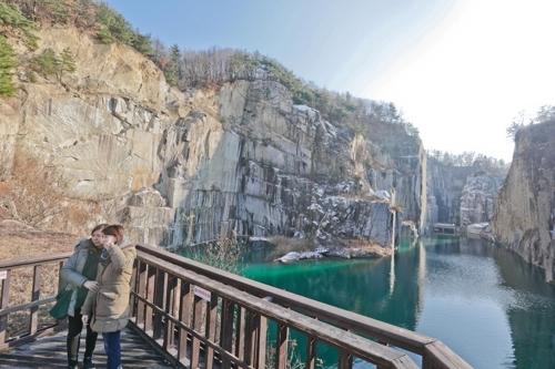 两位游客在方正的巨型绝壁与碧绿的湖水之间拍照留念。(韩联社记者成演在)