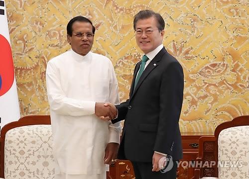11月29日,在韩国总统府青瓦台,总统文在寅同斯里兰卡总统西里塞纳(左)亲切握手。(韩联社)