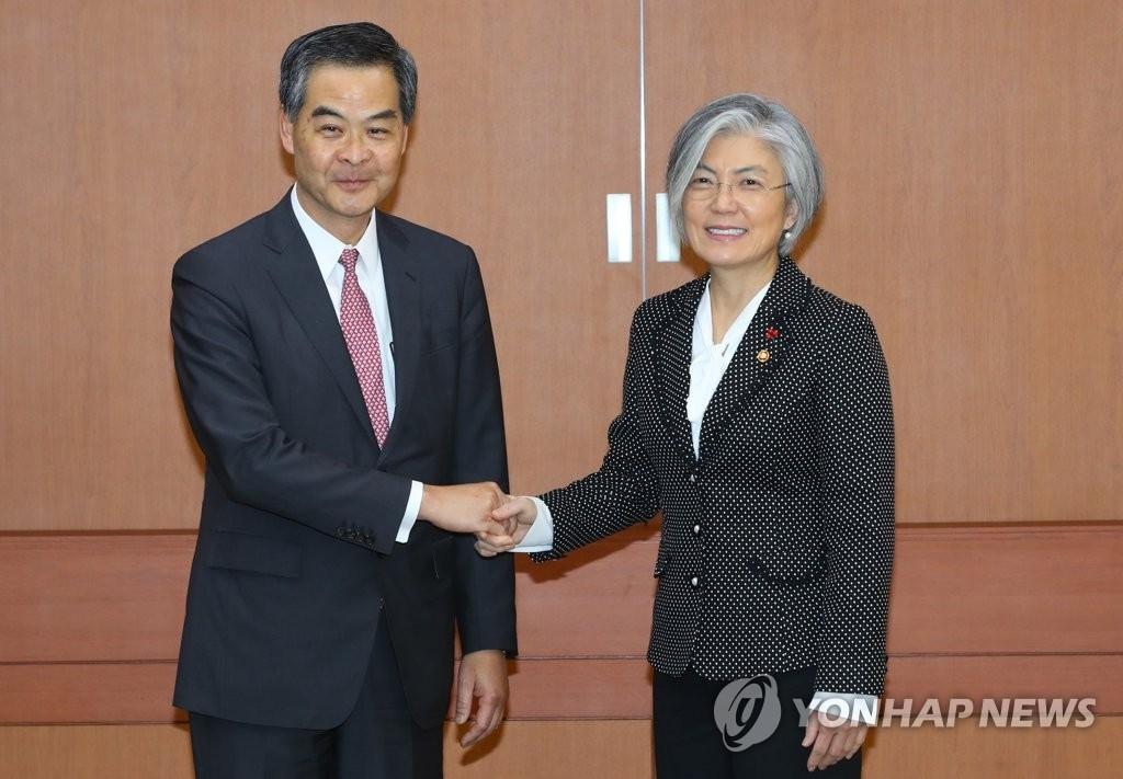 11月30日上午,在首尔外交部大楼,韩国外交部长官康京和(右)同中国人民政治协商会议副主席梁振英举行会谈前握手致意。(韩联社)