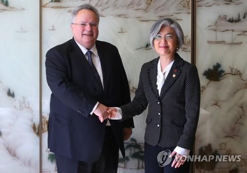 11月30日,在位于首尔小公洞的乐天酒店,韩国外交部长官康京和(右)同到访的希腊外长科恰斯举行会谈前握手合影。(韩联社)