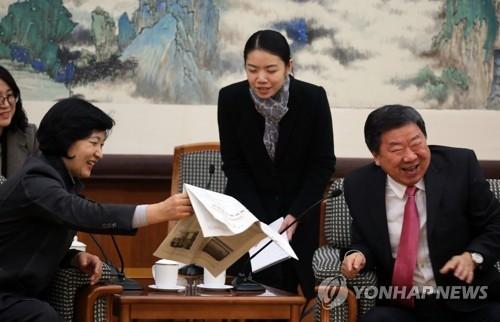 11月30日下午,在北京市的中共中央党校综合楼,何毅亭(右)给秋美爱看22日同框合影的照片,气氛亲切友好。(韩联社)