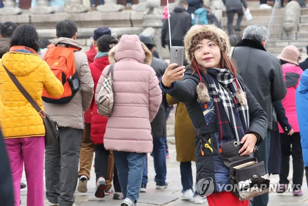 资料图片:中国游客在首尔景福宫自拍。(韩联社)
