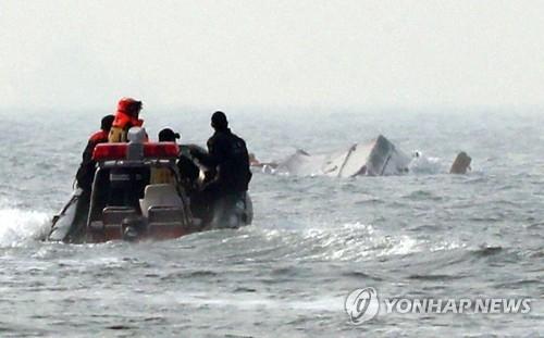 12月3日上午,在仁川市瓮津郡灵兴大桥以南2海里处,撞上燃油船后倾翻的钓鱼船正在沉入海面。(韩联社)