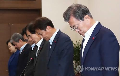12月4日下午,在青瓦台,文在寅(右一)主持召开首席秘书和助理会议前,为钓鱼船事故遇难者默哀。(韩联社)