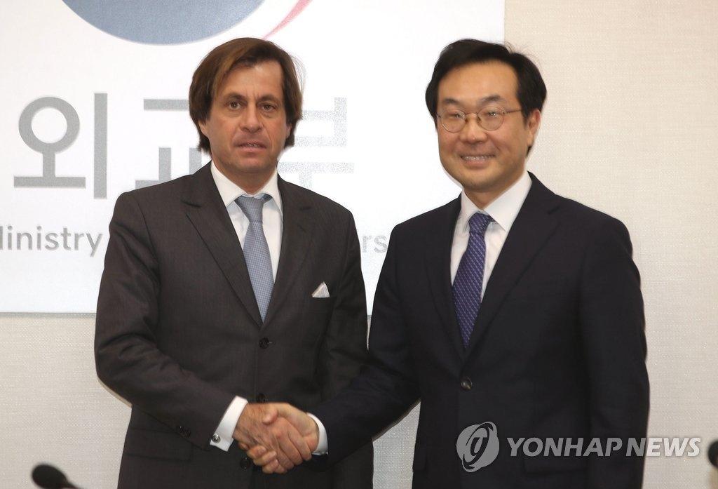 12月5日下午,在首尔韩国外交部大楼,外交部韩半岛和平交涉本部长李度勋(右)与法国外交部政治总司长尼古拉·德·里维埃举行会晤前合影。(韩联社)