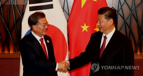资料图片:11月11日下午,在越南岘港,文在寅(左)和习近平在APEC峰会期间举行的首脑会谈上亲切握手。(韩联社)