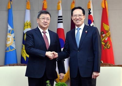 宋永武(右)和蒙古国防长恩赫包勒德握手。(韩联社/国防部提供)