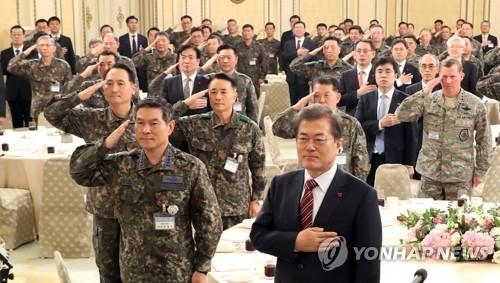 12月8日,在青瓦台,文在寅和全军主要指挥官向国旗敬礼。(韩联社)