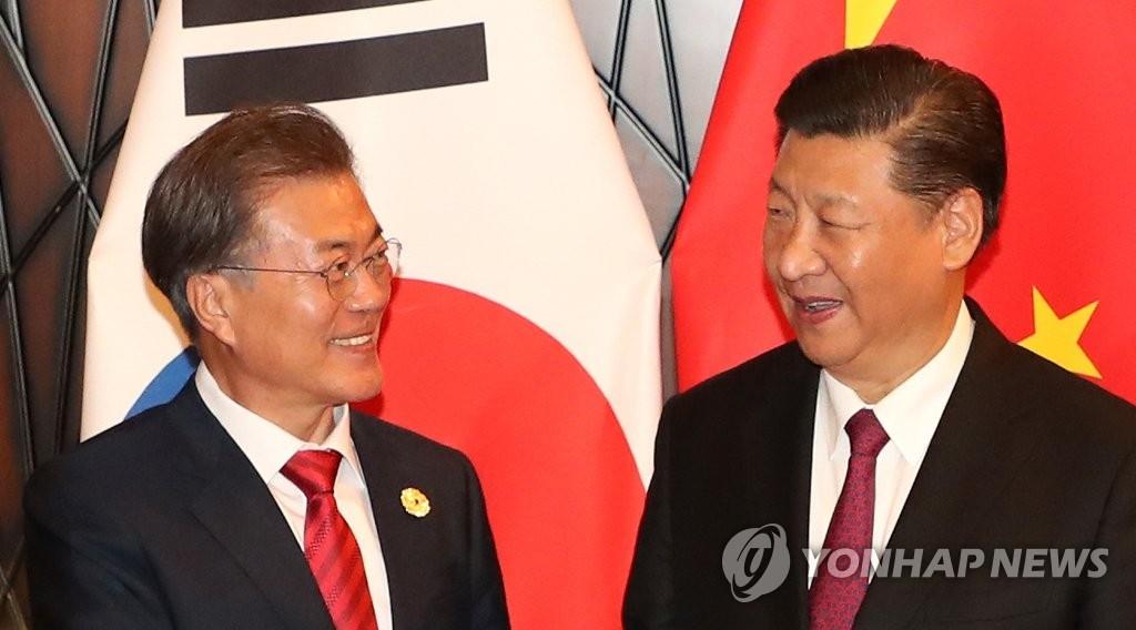 资料图片:11月11日,在亚太经合组织(APEC)领导人非正式会议上,韩国总统文在寅(左)与中国国家主席习近平举行首脑会谈。(韩联社)