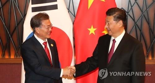 资料图片:11月11日,在亚太经合组织(APEC)领导人非正式会议期间,韩国总统文在寅(左)与中国国家主席习近平举行首脑会谈。(韩联社)
