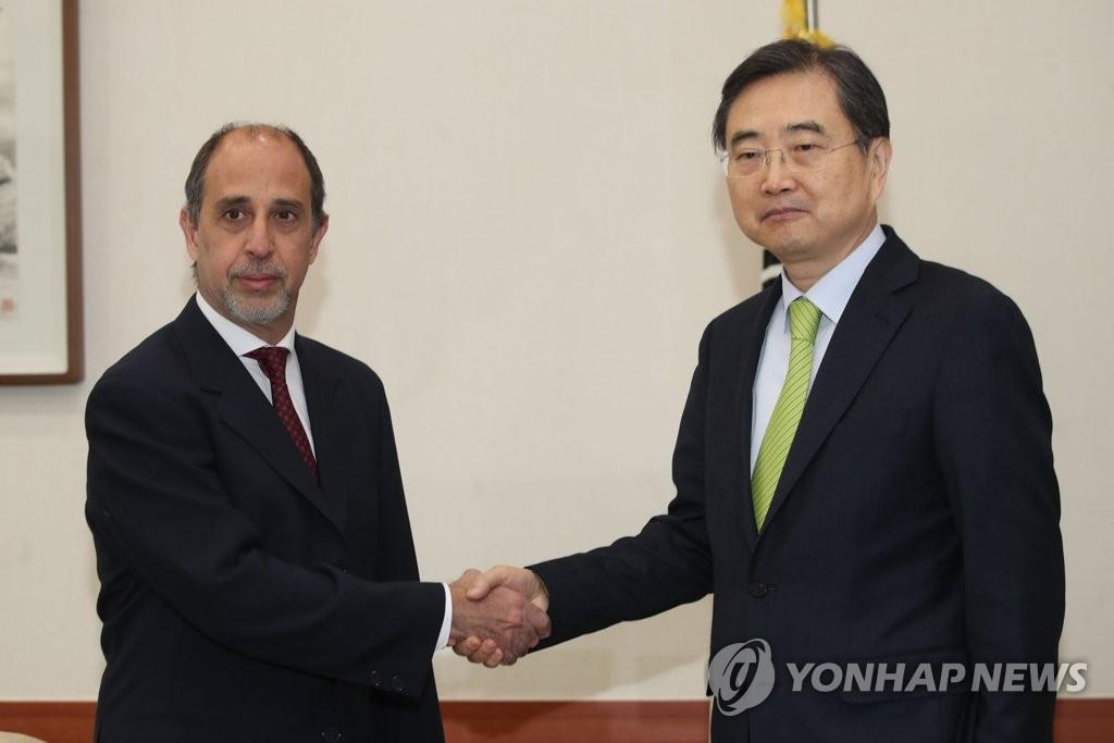 12月11日上午,在首尔韩国外交部大楼,外交部第二次官赵显(右)与到访的联合国朝鲜人权问题特别报告员托马斯•奥赫亚•金塔纳握手。(韩联社)