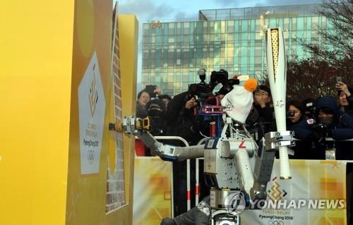 机器人DRC-HUBO钻墙传递奥运圣火。(韩联社)