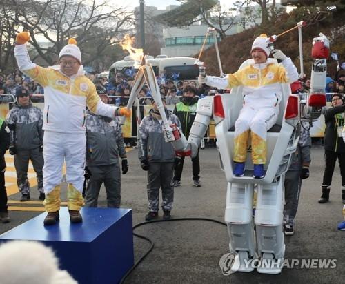 吴俊镐向机器人FX-2传递圣火。(韩联社)