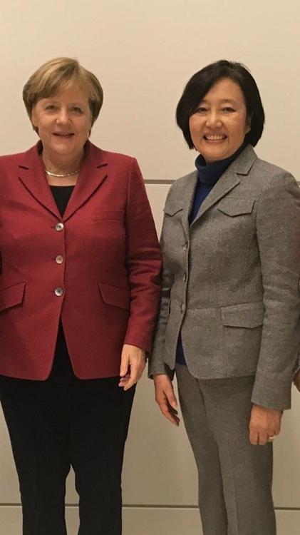 韩国共同民主党议员朴映宣(右)和德国总理默克尔合影。(韩联社)