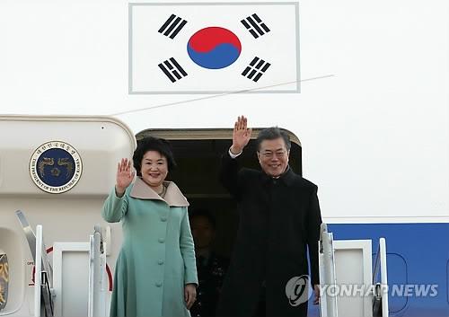 资料图片:12月13日,在位于京畿道城南市的首尔机场,韩国总统文在寅(右)和夫人金正淑女士在进舱前向欢送人群挥手致意。(韩联社)