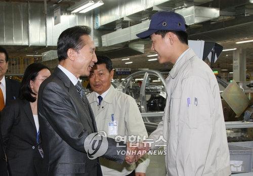 资料图片:2008年5月29日,在北京现代汽车工厂,李明博与一位员工握手。(韩联社)